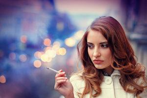 sad woman smonking cigarette on the balcony